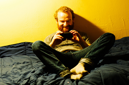 Photo of Bryon using cell phone on a bed, taken by David M. Goehring